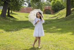 Девушка в белом платье с ажурным зонтиком на зеленой лужайке