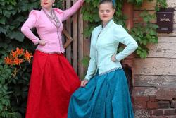 девушки в костюмах у деревянного дома