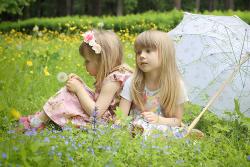Девочки на зеленой цветущей лужайке