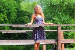 девушка в пестром платье на деревянном мостике над рекой