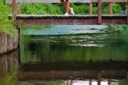 девушка в пестром платье на деревянном мостике